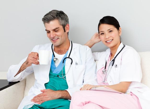 Positieve artsen die en koffie ontspannen drinken