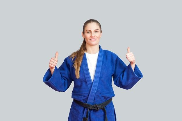 Positieve atletische karatevrouw in blauwe kimono met zwarte band die staat, duimen opsteekt en naar de camera kijkt met een brede glimlach. japans vechtsportenconcept. binnen, studio-opname, grijze achtergrond