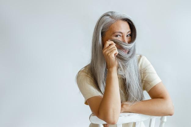 Positieve aziatische dame van middelbare leeftijd gebruikt grijs haar als niqab zittend op een stoel in de studio