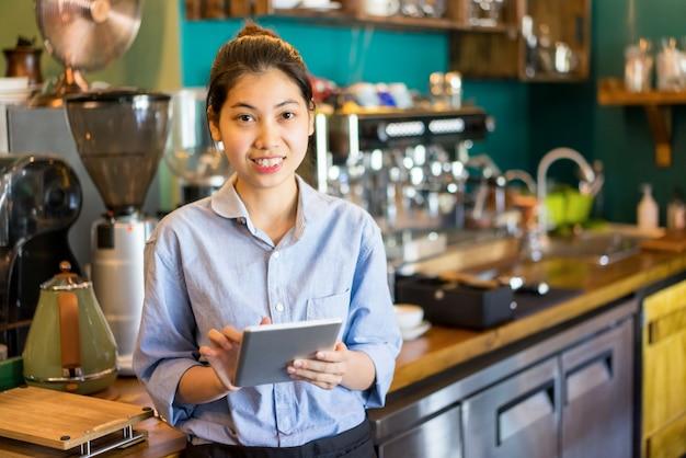 Positieve aziatische serveerster die tablet in koffiewinkel met behulp van en camera bekijkt.