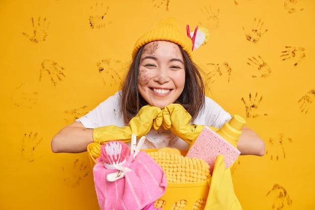 Positieve aziatische vrouw glimlacht positief en draagt hoed beschermende rubberen handschoenen poses in de buurt van wasmand geïsoleerd over gele muur