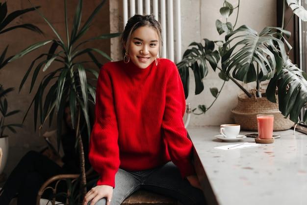 Positieve aziatische vrouw in rode trui en grijze spijkerbroek zit aan tafel in café
