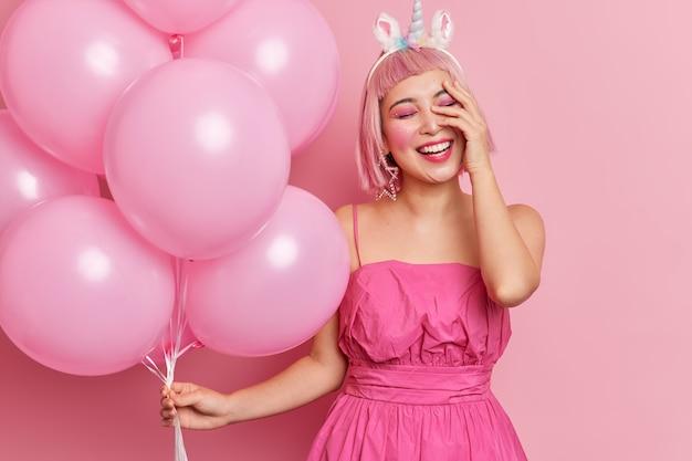 Positieve aziatische vrouw met roze haar giechelt positief houdt hand op gezicht heeft heldere professionele make-up draagt jurk heeft plezier op feestje houdt opgeblazen heliumballonnen