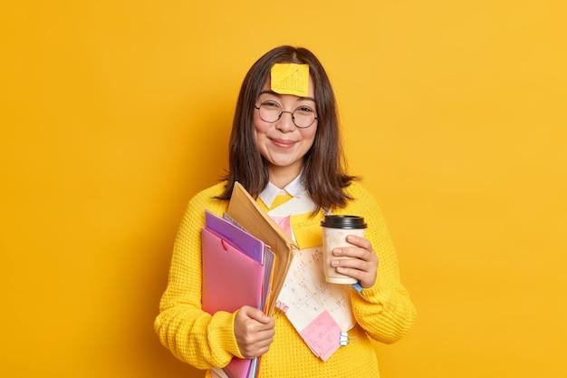 Positieve aziatische werkneemster houdt wegwerp kopje koffie houdt mappen heeft sticker met afbeelding geplakt op voorhoofd heeft pauze na examen leren.