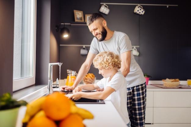 Positieve bebaarde man helpt zijn zoon om de afwas te doen