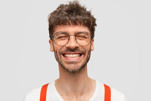 Positieve bebaarde man hipster glimlacht breed, heeft een tevreden uitdrukking, lacht om iets grappigs, sluit de ogen,