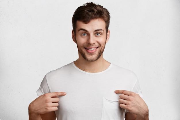 Positieve bebaarde man met stoppels, blauwe ogen en tevreden uitdrukking, geeft aan op lege kopie ruimte op t-shirt, geïsoleerd op witte achtergrond. mensen, goede gevoelens en advertentieconcept