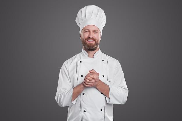 Positieve bebaarde volwassen man in uniform chef-kok glimlachend voor camera en handen wrijven tijdens het werken in restaurant tegen een grijze achtergrond