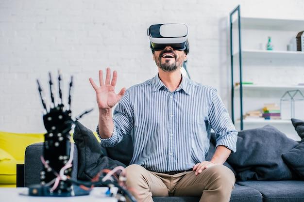 Positieve bebaarde volwassen man vr-bril tijdens het testen van robothand