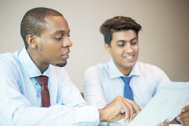 Positieve bedrijfsanalisten die financiële rapporten bestuderen