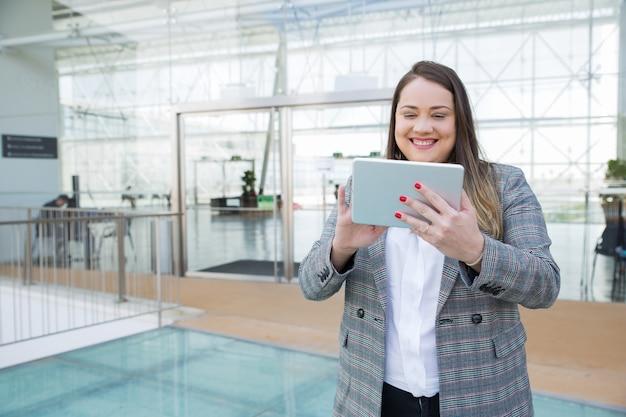 Positieve bedrijfsberoeps die aan tablet werkt