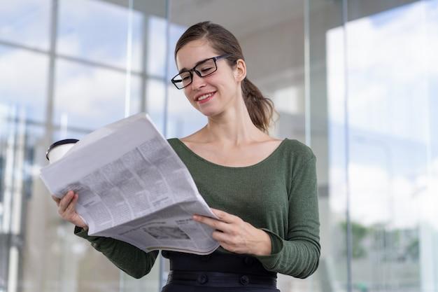 Positieve bedrijfsdeskundige die financieel nieuws controleert