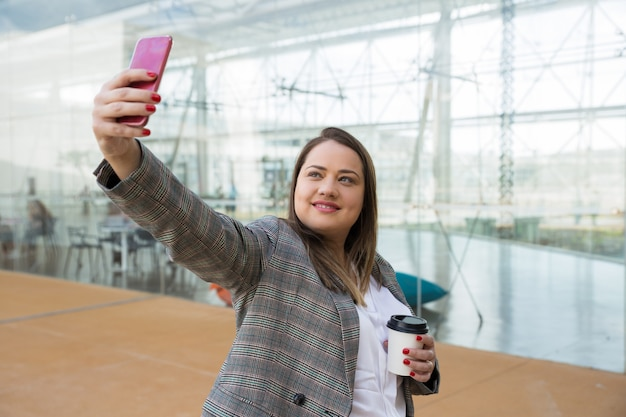 Positieve bedrijfsvrouw die selfie foto op telefoon in openlucht nemen