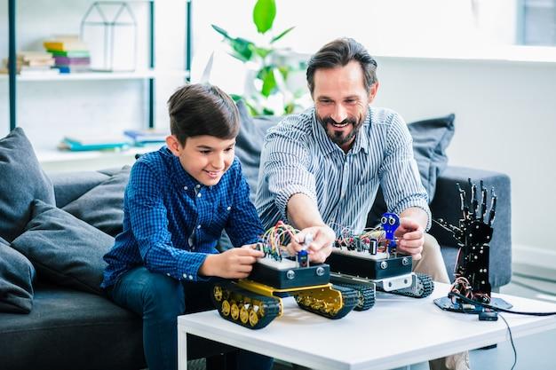 Positieve behulpzame vader en zijn slimme zoon die betrokken zijn bij robottechnologie terwijl ze thuis samen rusten