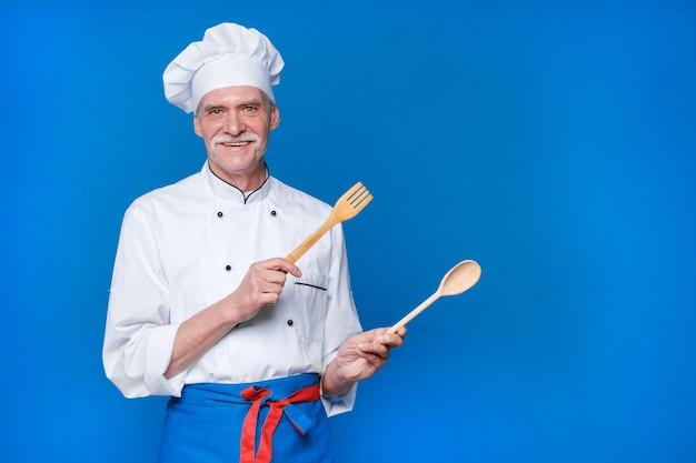 Positieve bejaarde chef-kok met houten lepel en vork, in wit uniform en pet poseren geïsoleerd op blauwe muur