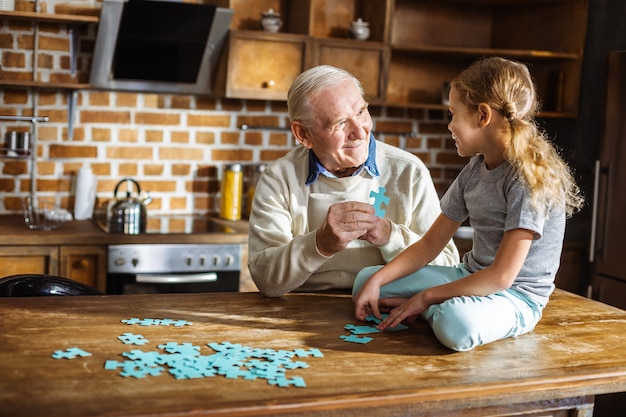 Positieve bejaarde man die een puzzel vasthoudt tijdens het samenstellen met zijn kleindochter