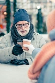 Positieve bejaarde man in warme kleren die buiten ontspant in de winterdag en kopjes koffie klettert met zijn vriend