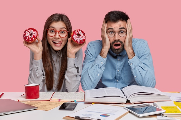 Positieve blanke jonge vrouw eet lekkere rode donuts, draagt een bril, gefrustreerd verbaasde ongeschoren man in formeel overhemd voelt zich het werk zat