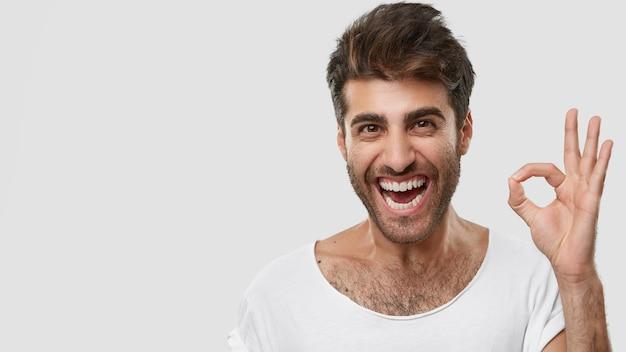 Positieve blanke man toont ok of nulteken, glimlacht van opwinding, voelt zich gelukkig