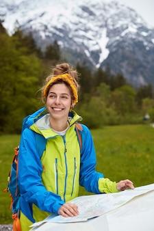 Positieve blanke vrouwelijke reiziger staat in de buurt van de kaart, bestudeert route, draagt gele sjaal op het hoofd, casual anorak