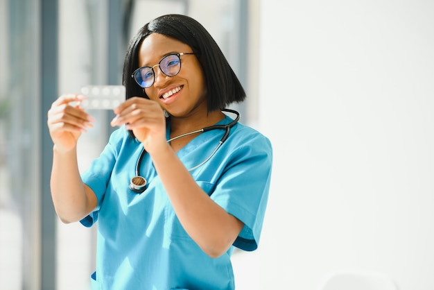 Positieve blije jonge afro-amerikaanse vrouw apotheker of arts, die in handen pillen