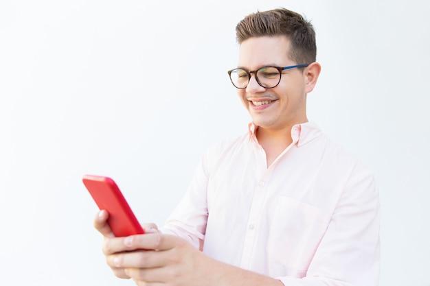 Positieve blije man in bril lezen bericht op telefoon