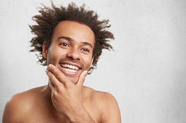 Positieve blije man met donkere huid, houdt de hand op de kin, herinnert zich prettige momenten in het leven