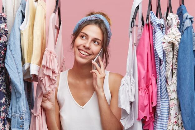 Positieve blije vrouw met aangename glimlach, gesprek via slimme telefoon terwijl je tussen hangers met kleren. het gelukkige wijfje kleedde terloops glimlachend terwijl het spreken over mobiele telefoon