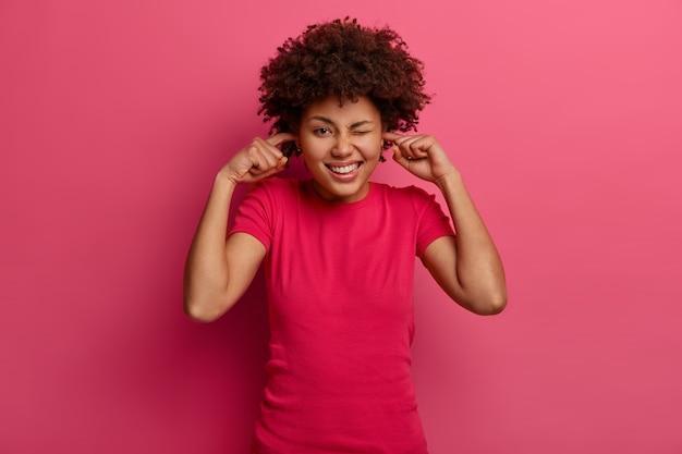 Positieve blije vrouw stopt oren met wijsvingers en knipoogt, vermijdt hard geluid, heeft afro-kapsel, gekleed in vrijetijdskleding, poseert over roze muur. zo luidruchtig hier. zet muziek alstublieft uit