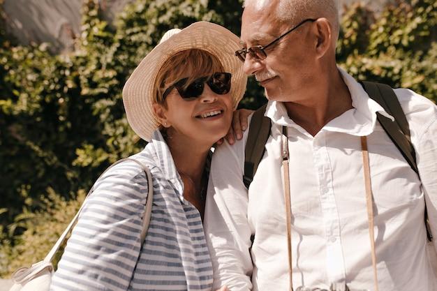 Positieve blonde dame in zonnebril, blauwe kleding en hoed glimlachend en poseren met grijze harige man in wit overhemd buiten.