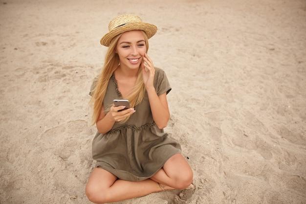 Positieve blonde langharige mooie vrouw zittend op zand met gekruiste benen, smartphone in de hand houden en breed glimlachen, haar gezicht aanraken met opgeheven hand