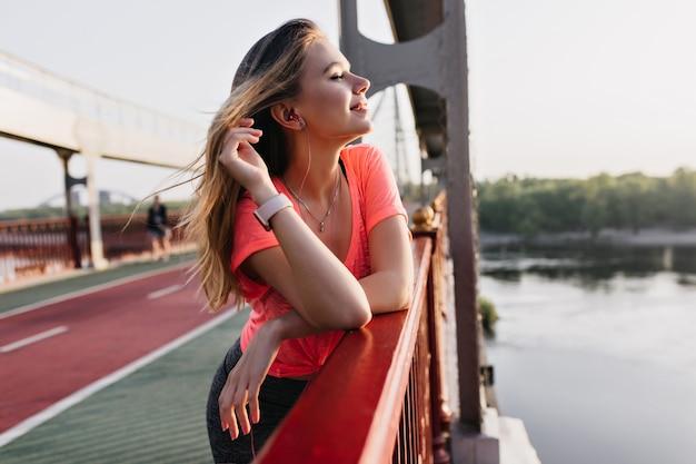 Positieve blonde meisje luisteren muziek na de training. prachtige blanke vrouw ontspannen in goede zomerochtend.
