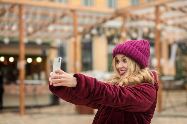 Positieve blonde vrouw die plezier heeft en zelfportret maakt op de achtergrond van de slinger in kiev