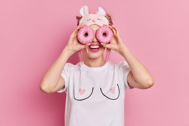 Positieve blonde vrouw houdt heerlijke geglazuurde donuts over ogen glimlacht toont in grote lijnen perfecte tanden