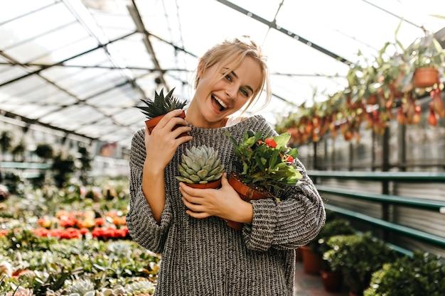 Positieve blonde vrouw in gebreide jurk lacht vrolijk, poseren met verschillende evergreens in kas.