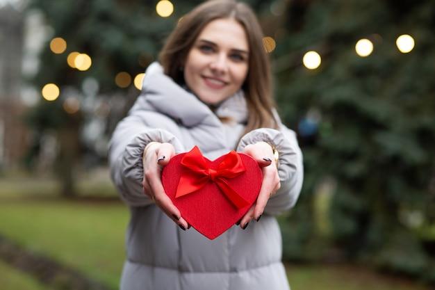 Positieve blonde vrouw met een geschenkdoos op straat. achtergrond vervagen