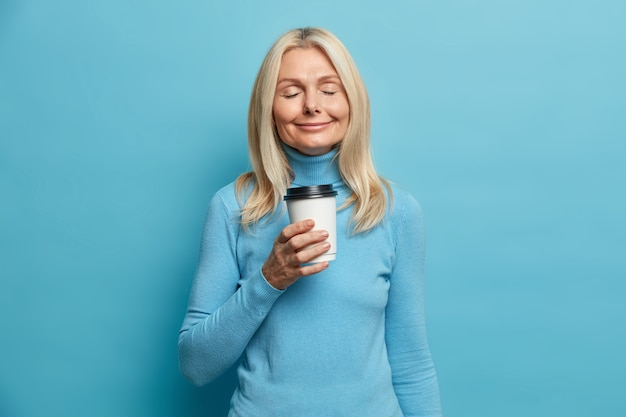 Positieve blonde vrouw staat met gesloten ogen drinkt afhaalkoffie