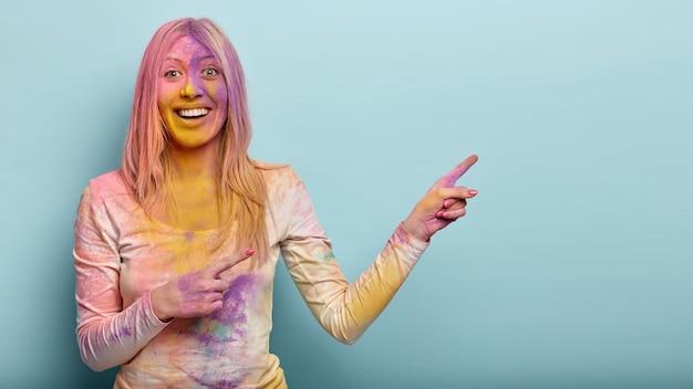 Positieve blonde vrouw vuil met kleurrijke poeder, iets op lege ruimte adverteert, lacht vrolijk, geniet van indiase fest, geïsoleerd tegen blauwe muur. promotie concept