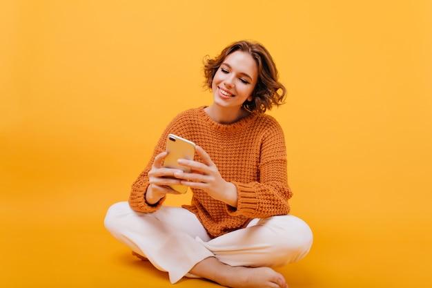 Positieve blootsvoets meisjeszitting met telefoon op de vloer