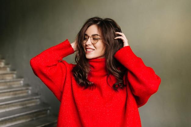 Positieve brunette in een goed humeur raakt haar lange krullende haar aan. meisje in stijlvolle oversized trui poseren op grijze muur.