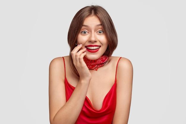 Positieve brunette jonge vrouw poseren tegen de witte muur