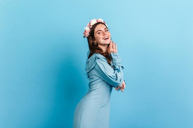 Positieve brunette met bloemen in krullend haar lacht, poseren in satijnen jurk op blauwe muur.