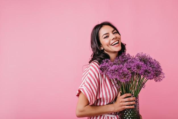 Positieve brunette met kuiltjes straalt vreugde uit. momentopname van schattige krullende dame met mooie enorme paarse bloemen.