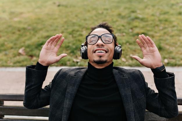 Positieve brunette mulat man ochtend buiten doorbrengen en muziek luisteren. foto van knappe afrikaanse man in zwart pak zittend op een bankje voor groen gazon.
