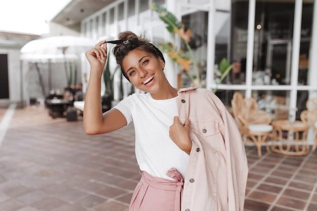 Positieve brunette vrouw in wit t-shirt en roze jasje raakt haar haarband en glimlacht tegen muur van caféterras
