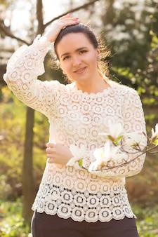 Positieve brunette vrouw met naakt make-up, kanten blouse dragen, poseren in de buurt van de bloeiende magnolia bloemen
