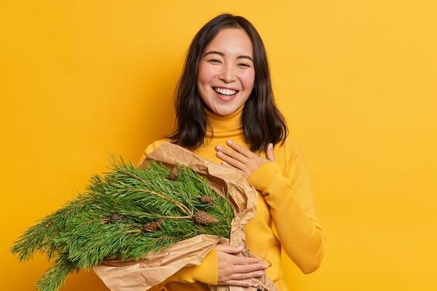 Positieve brunette vrouw met oosterse uitstraling houdt kerstboom fir takken met dennenappels drukt gelukkige oprechte emoties uit