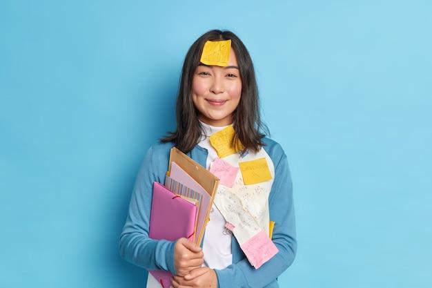 Positieve brunette vrouwelijke secretaris draagt mappen met documenten draagt blauwe trui met plaknotities geschreven bedragen.