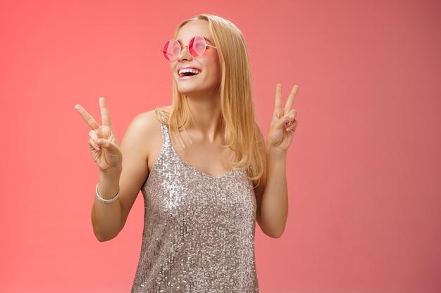 Positieve charmante europese zorgeloze stijlvolle vriendin die plezier heeft dansvloer toon overwinning vredestekens kijk vrolijk op glimlach in zonnebril glamour glinsterende jurk geniet van feest, rode achtergrond.