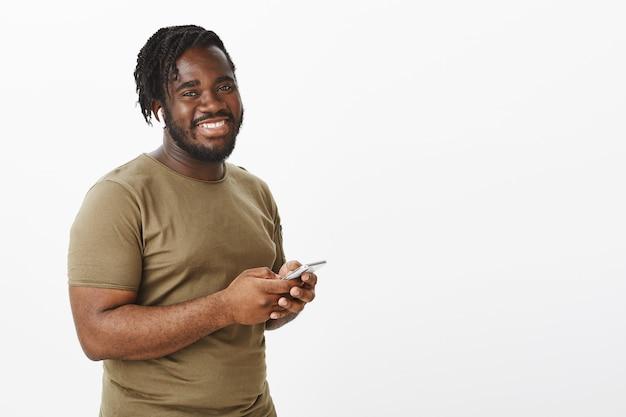 Positieve charmante man in een bruin t-shirt poseren tegen de witte muur met zijn telefoon